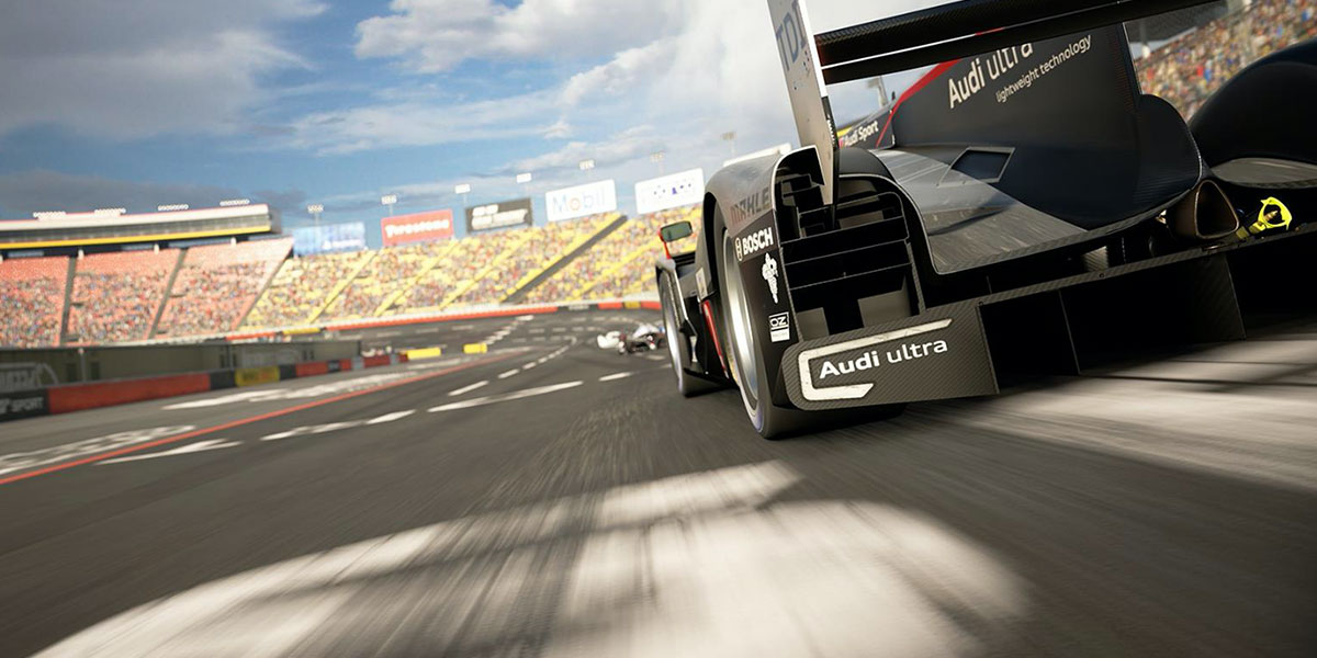 Still image showing the tail of a Audi race car driving around a track in a video game