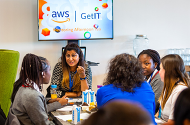 Group of women sitting around a table talking with the 'AWS GetIT' logo on a TV screen behind them.