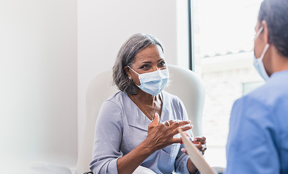 An older woman patient wearing a mask talking to a doctor who is also wearing a mask.