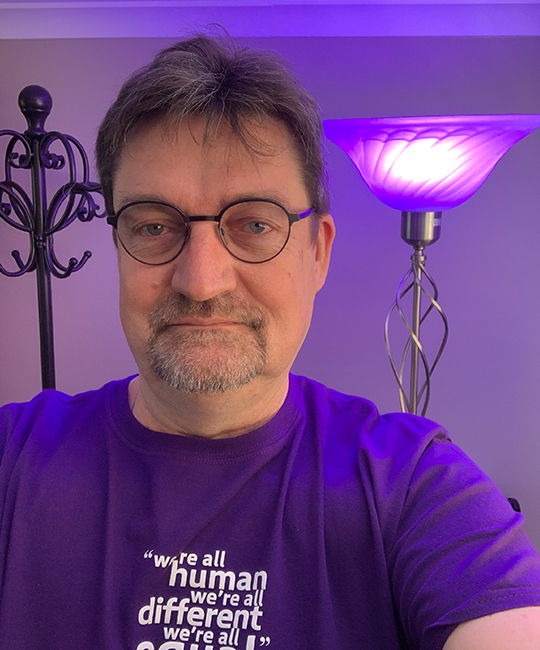 Man wearing a purple shirt with a purple lamp in the background.