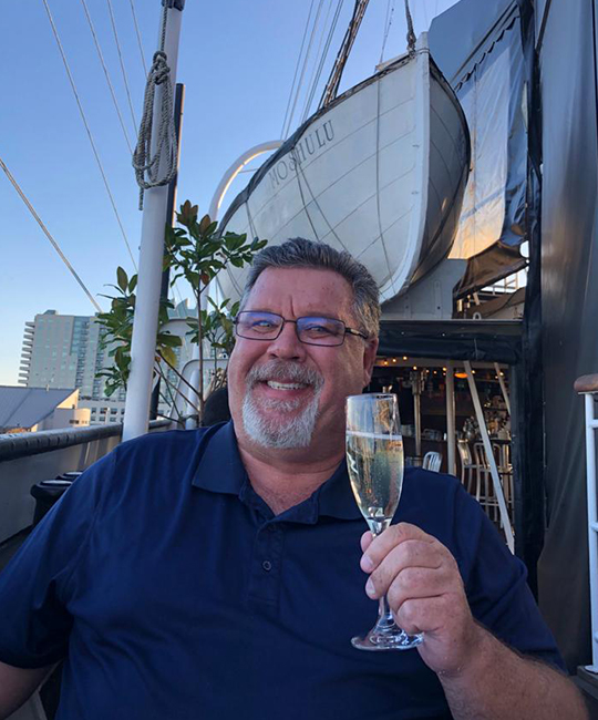 Man smiling at the camera, holding up a glass of champagne.