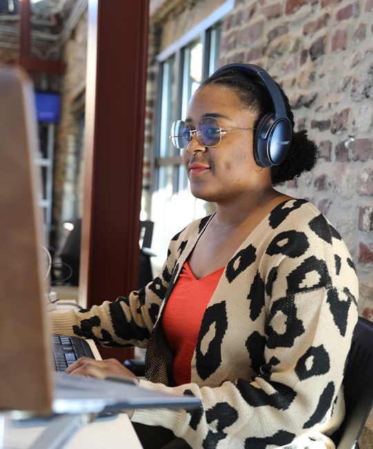 Woman wearing headphones, sitting at her computer.