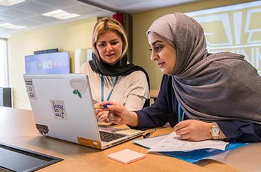Two women, one of whom is wearing a hajib, sitting at a table looking at a laptop together.