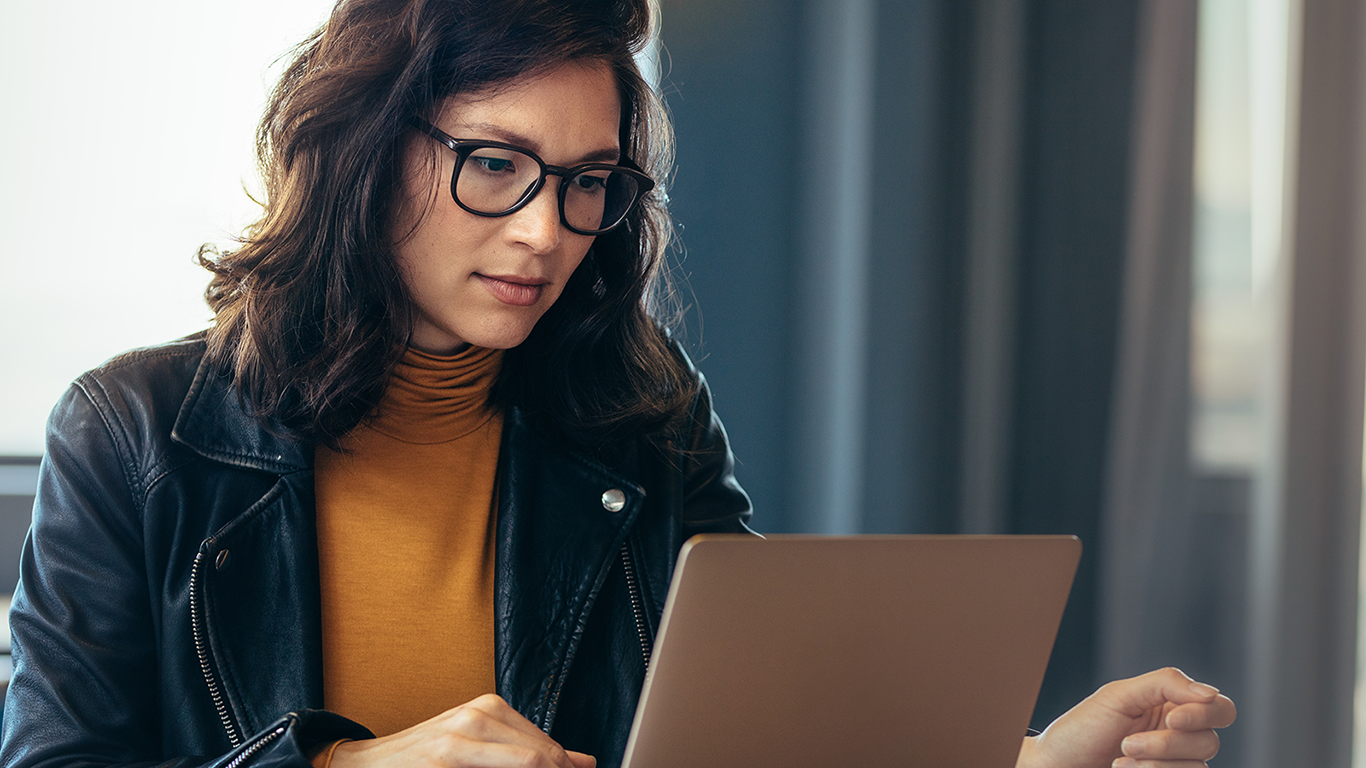 A woman wearing eyeglasses is sitting at a desk with a laptop and learning how to run security applications in the AWS Cloud.
